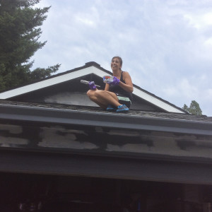 Tami Fischer on the roof with paintbrush in hand