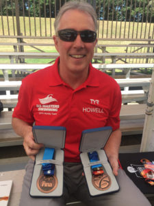 Rick Howell and his two FINA medals. Congratulations, Rick! Keep up the great swimming!!